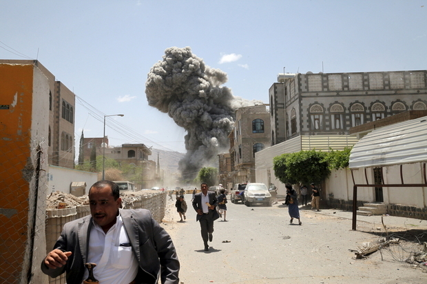 People flee as smoke billows after air strikes hit the house of Yemen's former President Ali Abdullah Saleh in Sanaa