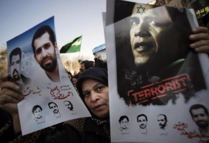 FILE PHOTO: A worshipper holds an anti-U.S. President Barack Obama poster and portraits of killed Iranian nuclear scientists in Tehran