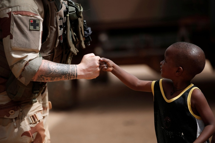 A French soldier greets a child as soldiers conduct a CIMIC (Civil-Military Co-operation) patrol during the regional anti-insurgent Operation Barkhane in Gao