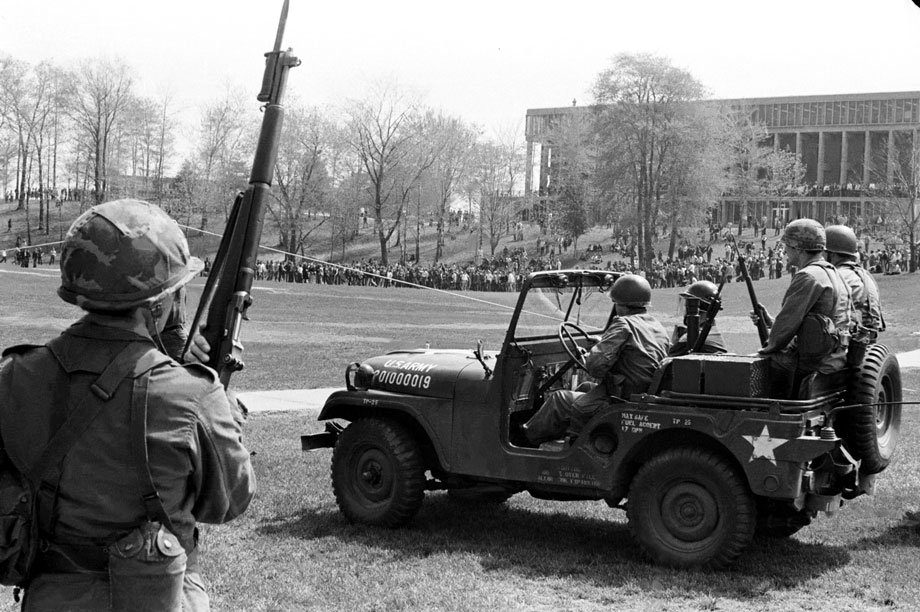 Guardsmen watch from a distance as students gather in the common